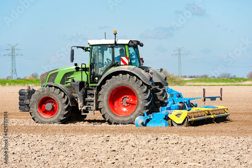Obraz na plátně Tractor with power harrow in the field during soil cultivation 1297