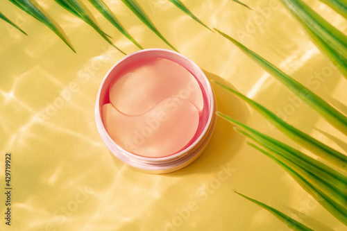 Fotografiet Pink jar with hydro gel eye patch on yellow background with palm leaves and water highlights