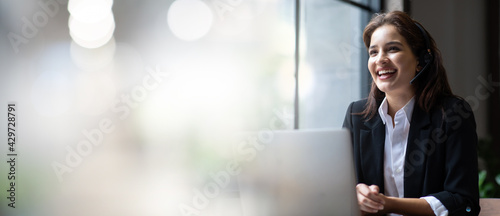 Fotografie, Obraz Attractive business woman Asian in suits and headsets are smiling while working with computer at office
