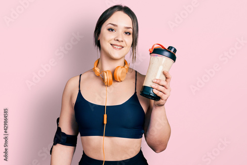 Stampa su Tela Young hispanic girl wearing sport clothes drinking a protein shake looking posit
