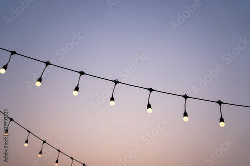 Tablou Canvas Light bulb decor,Garlands of lamps on a wooden stand on the street,Lights hang o