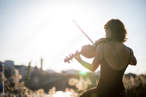 Slika na platnu Young woman violinist posing playing on the street during sunset close up