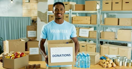 Cuadros en Lienzo Portrait of young African American handsome cheerful guy volunteer standing in w