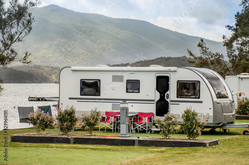 RV caravan camping at the caravan park on the lake with mountains on the horizon Fototapet