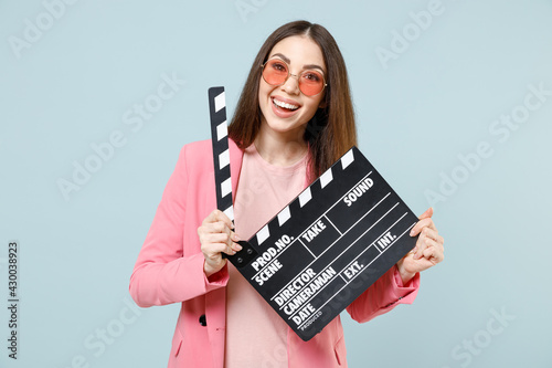 Fotografiet Young friendly fun smiling cheerful happy woman 20s wear pastel pink clothes glasses holding classic black film making clapperboard isolated on blue color background studio