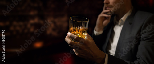 Obraz na plátně man wearing suit sits in the luxury bar in gentlemen club and drink whiskey