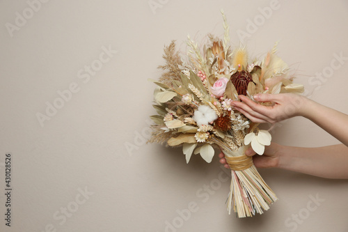 Fotografia, Obraz Woman holding beautiful dried flower bouquet on beige background, closeup