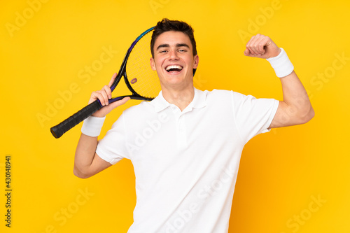 Carta da parati Handsome teenager tennis player man isolated on yellow background playing tennis