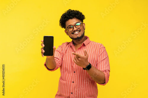 Canvas Print Smiling indian guy isolated on yellow background holding smartphone with black screen in hand and pointing finger at it, looking at camera, place for text