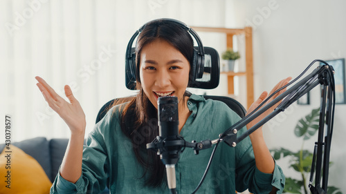 Photo Happy asia girl record a podcast with headphones and microphone look at camera  talk and take a rest in her room