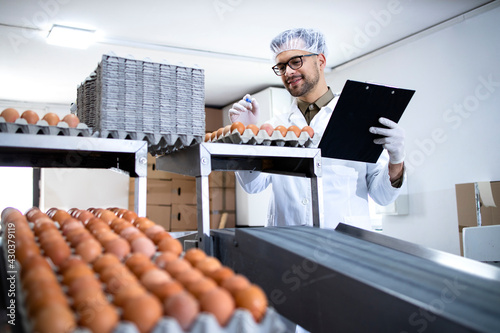 Canvas-taulu Factory worker holding checklist inspecting and checking quality of chicken eggs at food processing plant