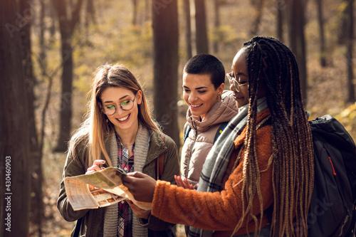 Obraz na plátne Three female friends having fun and enjoying hiking in forest.