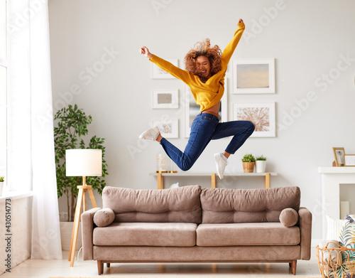 Fototapeta Happy african american teen girl jumping on sofa while having fun on weekend at