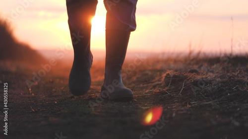 Fotografiet Farmer goes with rubber boots along green field