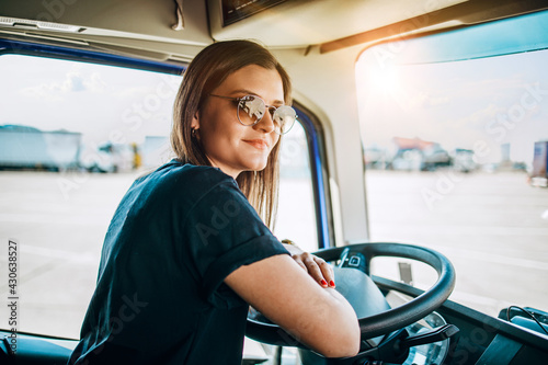 Fotografie, Obraz Portrait of beautiful young woman professional truck driver sitting and driving big truck