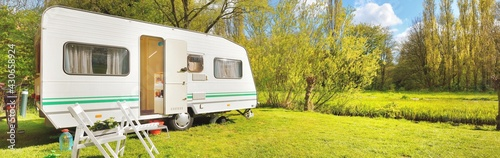 Canvas White caravan trailer on a green lawn in a camping site