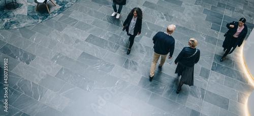Obraz na plátne People walking through a office hallway