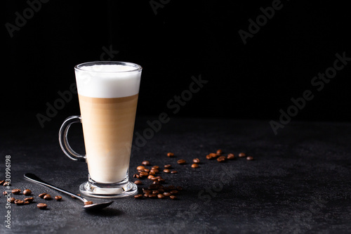 coffee with milk, latte macchiato in a glass with a handle and a long spoon on a Poster Mural XXL