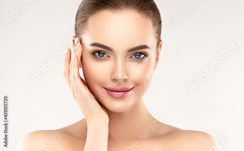 Fotografiet Beautiful young woman with clean fresh skin touching her face