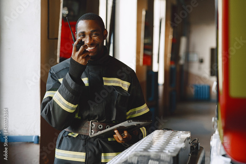 Canvas-taulu Portrait of a firefighter standing in front of a fire engine