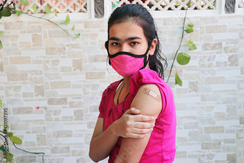 Fotografija Indian girl shows a bandage applied after getting vaccination during new strain of covid-19, young teenager wearing mask received a coronavirus vaccine on her arm