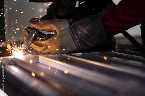 Obraz na plátně Welders wear safety gloves when welding. Close up