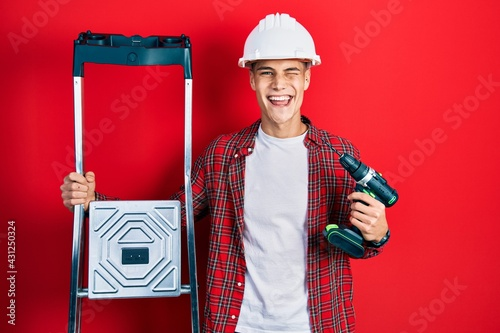 Young hispanic man holding screwdriver wearing hardhat by construction stairs winking looking at the camera with sexy expression, cheerful and happy face Fototapeta