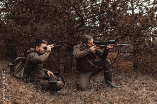 Fotografia Two hunters are hunting in the forest, one is kneeling and aiming, the other is