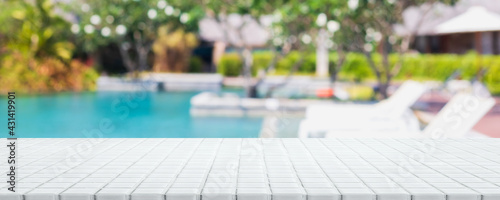 Fotografie, Obraz Empty white ceramic mosaic table top and blurred swimming pool in tropical resort in summer banner background - can used for display or montage your products