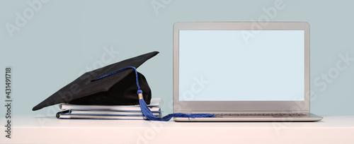 Fotografering Graduation Cap on notebooks near laptop
