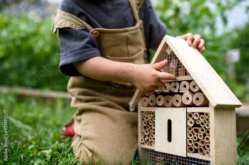Foto Obscured small child playing with bug and insect hotel in garden, sustainable lifestyle