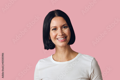 Leinwand Poster Studio portrait of brunette smiling looking at camera