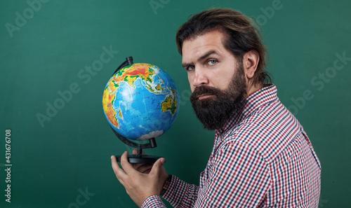 Photo mature bearded man teacher in school classroom with blackboard, geography