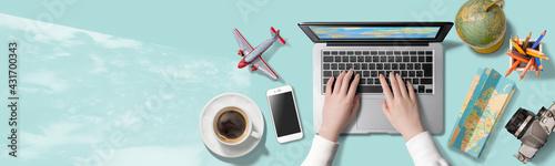 Obraz na plátně ノートパソコンをタイピングする手。海外旅行にまつわるアイテム。旅行の計画をたてているところ。もしくは、インターネットで旅行の疑似体験をしているところ。真上からの