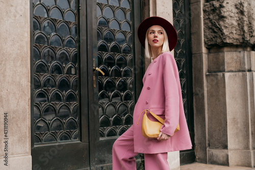 Fotografia Street style, fashion conception: elegant woman wearing trendy pink suit, burgundy color hat, holding yellow bag, posing in street of city
