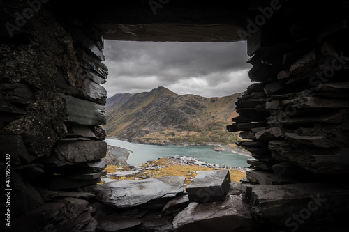 Fototapeta Beautiful view of mount Snowden landscape through window of abandoned miners bothie cottage in Dinorwic slate quarry North Wales