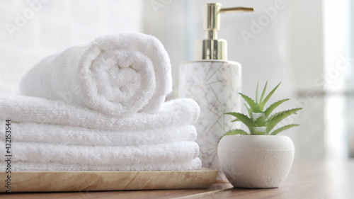 Fotografie, Obraz close up ofTowel placed on basket, white table top, bottle of liquid soap, spa set for bathing in the bathroom, copy space, bathroom window