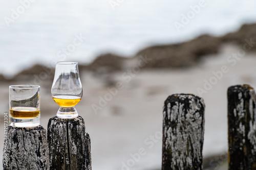 Canvas Print Tasting of dram single malt scotch whisky on seashore in Scotland, old wooden po