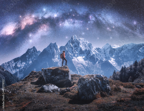 Arched Milky Way and sporty woman on the stone and mountains in snow at night. Girl with backpack, sky with bright stars, snowy rocks in Nepal. Space. Landscape with milky way arch. Travel and hiking