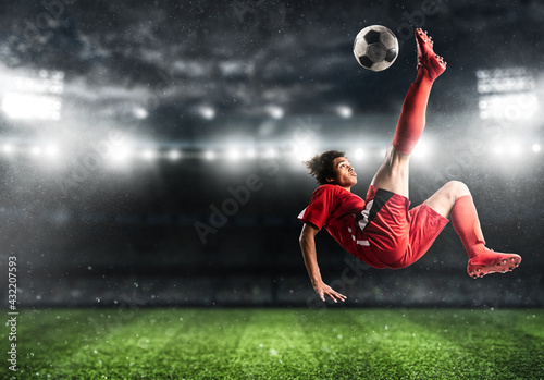 Soccer striker in red uniform hits the ball with an acrobatic kick in the air at Fototapeta