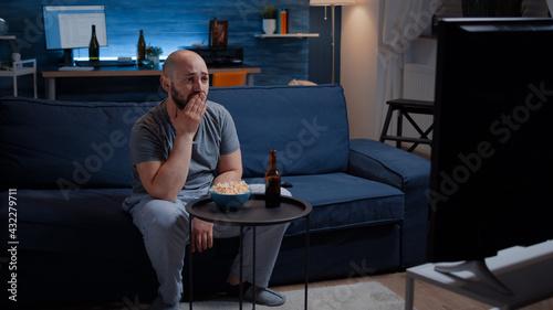 Obraz na płótnie Focused man looking at drama movie, crying sitting on sofa eating popcorn late night