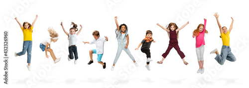 Fotografia, Obraz Group of elementary school kids or pupils jumping in colorful casual clothes on white studio background