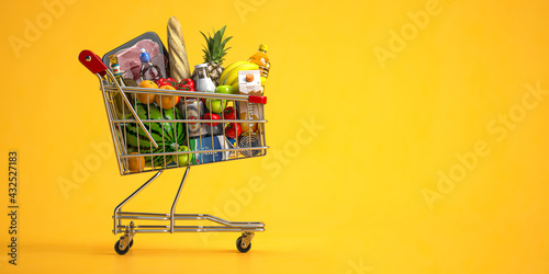 Cuadros en Lienzo Shopping cart full of food on yellow background
