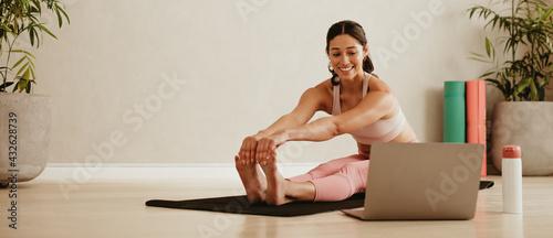 Woman doing yoga watching video on laptop