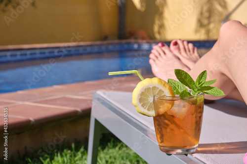Canvas Woman legs on deck chair with cocktail at the edge of swimming pool