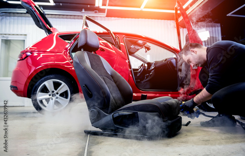 Car service worker cleaning car seat with a steam cleaner