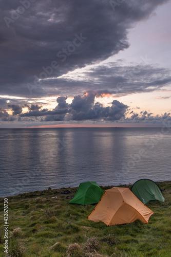Fotografiet three tents on cliffs at dawn in greystones ireland
