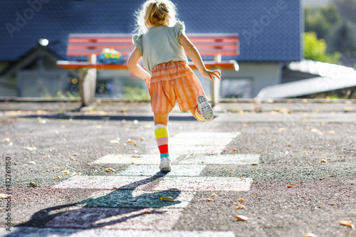 Fényképezés Cute little toddler girl playing hopscotch game drawn with colorful chalks on asphalt