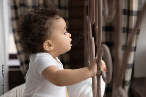 Fotografie, Obraz Cute little African American girl toddler child stand holding bed frame look in distance feel curious
