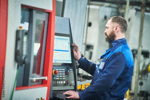 Industrial worker operating cnc machine at metal machining industry Fototapet